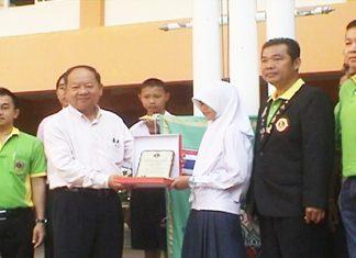 Nongprue Mayor Mai Chaiyanit presents a plaque to painting contest winner Sara Yimwilai.