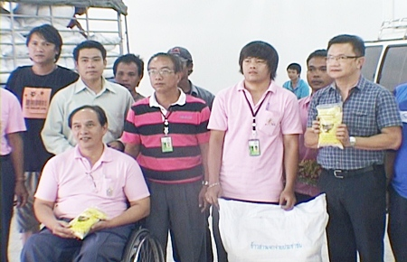Deputy Mayor Wutisak Rermkitkarn, right, helps volunteers distribute rice to 19 orphanages, shelters and disabled centers in the Pattaya area.