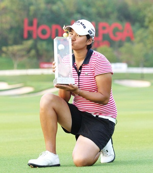 Yani Tseng poses for the assembled media holding the champion's trophy.