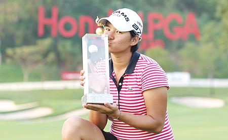 Yani Tseng of Taiwan holds up the 2011 Honda LPGA Thailand champion's trophy after shooting a final round 66 to win the tournament by 5 shots.
