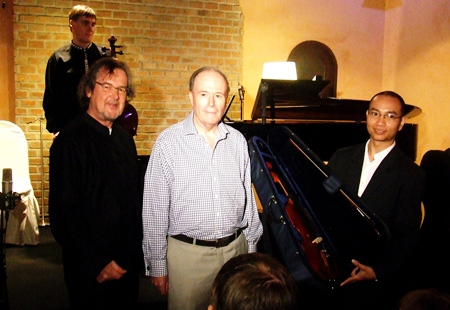 Composer Richard Harvey, left, and SCO co-founder John Pawson, center, stand with Chiang Rai Youth Orchestra's Paramet Lertkasem after he is presented with the new musical instruments.