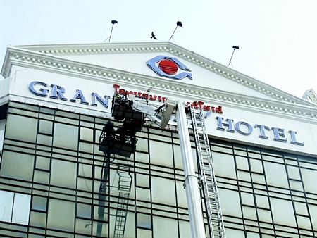 Workers remove a dangerous façade on the Grand Sole hotel in Pattaya, Feb. 24, as part of major renovation works at the establishment.