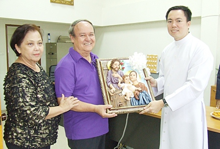 Father Francis Xavier Kritsada Sukkaphat presents an exquisite framed holy sculpture of the Nativity scene to Supanee and Premprecha Dibbayawan.