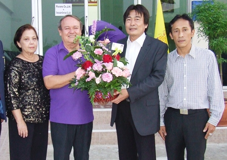 Deputy Mayor Ronakit Ekasing presents a bouquet to Prem and Supanee.