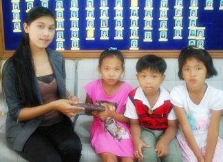 Supanida Chairat, 8, Korakot Arun, 6, and Chonthicha Khempet, 7, return the lost purse to Tasanee Pha-Indee.