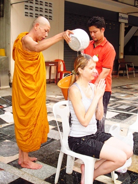 Thepprasit Temple's Assistant Abbott Bunsong Jantimo pours holy water over Kristina to turn bad luck to good.