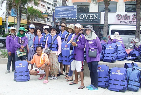A handful of Korean tourists model the new life jackets as tour employees prepare to hand out hundreds of the safety devices during the day.
