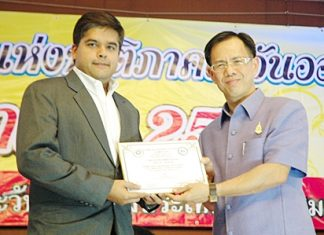 """Suwanthep Malhotra Pattaya Mail's Assistant MD (left) receives the prestigious """"Most Outstanding Mass Media of the Year"""" plaque from Chonburi Vice Governor Pongsak Preechawit."""