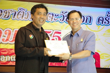 Visal Saengjaroen (left) of Channel 7 receives his plaque for the best photographer in biographical news from Chonburi Vice Governor Pongsak Preechawit.