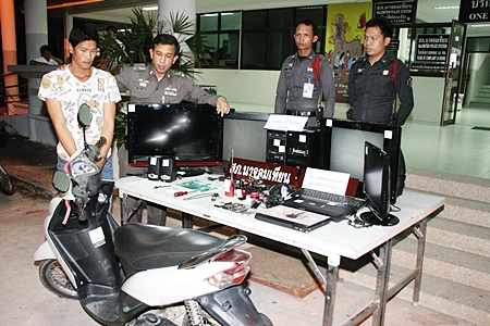 Police bring out for the cameras Ampol Saree (left), accused of stealing the Yamaha Mio and electronic equipment displayed in front of him.