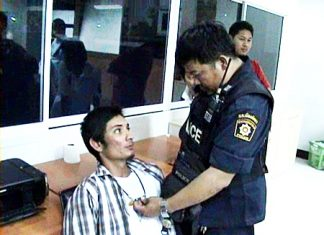 Finlip Kongnoi, seated, is held for questioning at Pattaya Police Station, Tuesday, March 1.