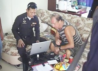 Police check Karstein Abrahamsen's laptop computer for any incriminating evidence following his arrest at the K2M Apartments in Pattaya on Tuesday, March 1.