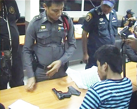 Nopporn Kesatcha (seated) is asked to give an explanation for the 11mm. pistol found in his possession.