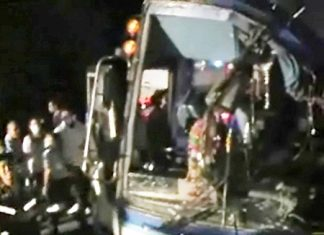 Rescue workers struggle to free injured passengers from the badly damaged tour bus.