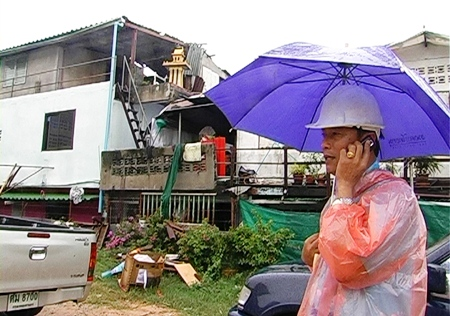 A city official inspects property in South Pattaya for signs storm damage.