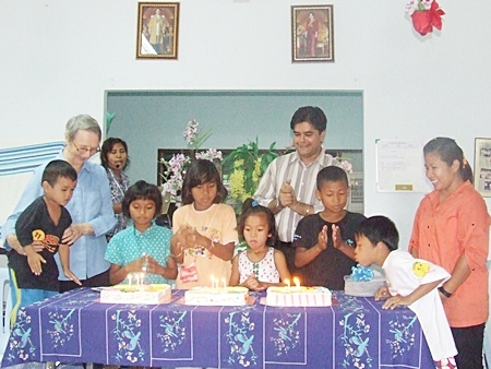 Sister Joan and Tony cheer as the birthday children blow out the candles on the birthday cakes.