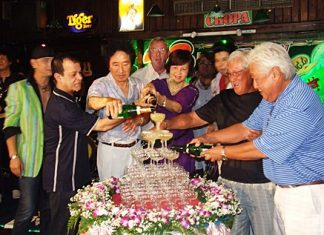 Diana Group Managing Director Sopin Thappajug, center, helps start the champagne waterfall as part of the 23rd anniversary celebrations for the Green Bottle Pub.
