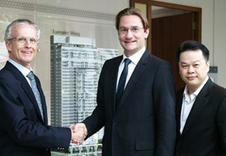 Bouygues Thai Managing Director Jean-Marie Verbrugghe, left, shakes hands with Raimon Land's Chief Executive Officer Hubert Viriot, center, as Raimon Land Chief Operating Officer Kitti TungSriwong looks on.