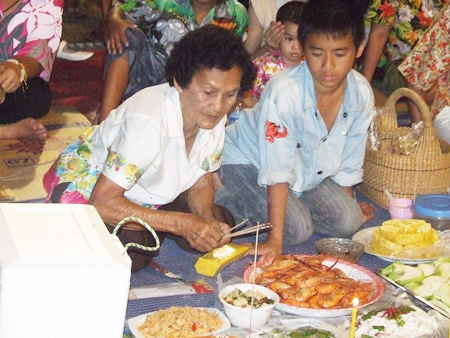 Naklua residents, young and old, prepare food and desserts for the spirits.