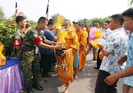 Enlisted men and officers present offerings of rice, dried food and other items to monks from Rangsri Sunthorn Temple.