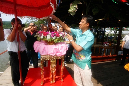 Rear Adm. Tharathorn Kachitsuwan sprinkles water on the Buddha to make merit during the traditional Songkran ceremony.