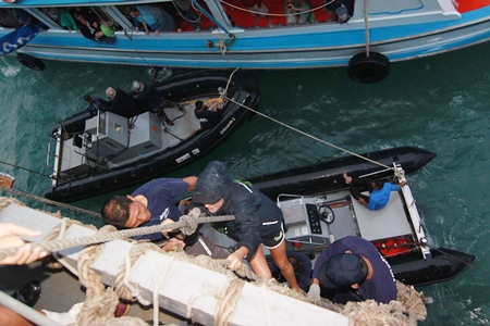 Tourists are hoisted aboard the HTMS Chakri Naruebet just off the coast of Koh Tao.