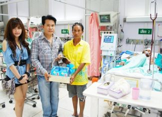 Monsit Kamsroi (center) and Am-Nantiya Sri-Ubon (left) present a gift basket to Suchat's mother, Pairat Kampanon. The injured Suchat (right) remains unresponsive.
