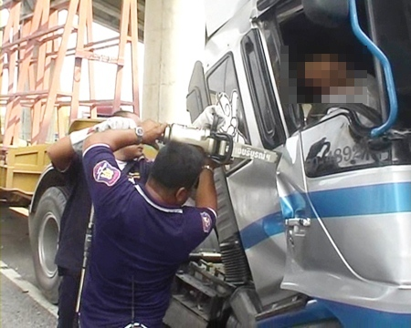 Rescue workers struggle to free the body of Ekachai Cholmak from the cab of his vehicle after it struck another lorry on Highway 38 Wednesday.