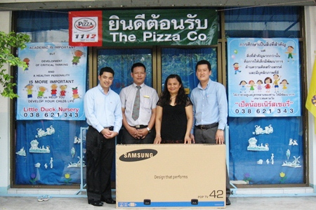 Tic (second right) receives the Little Duck Nursery's new television.