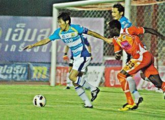 Pattaya United (blue shirts) defend against Si Sa Ket FC at the Sri Nakhon Lamduan Games stadium in Si Sa Ket, Sunday, April 24.