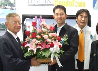 Pakorn Thavisin, left, Chairman LPN Development Public Company Ltd., receives a bouquet of flowerers from Pattaya Mayor Ithiphol Khunpluem congratulating him on the launch of the project.