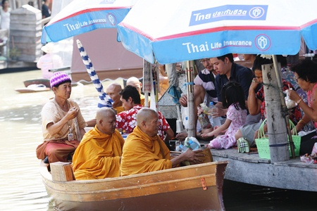 Monks arrive by boat to receive alms at Pattaya's Floating Market.