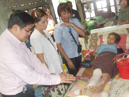 Deputy Mayor Verawat Khakhay and a doctor from the city Social Welfare Department visit Sa-nuan Pansuwan as part of the city's medical outreach program.
