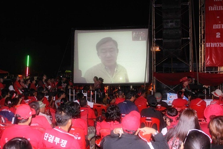 UDD enthusiasts listen to a call in from self-exiled leader Thaksin Shinawatra.