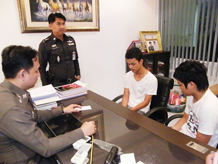 Thanawat Pornjit-udom and Pirapong Boonkor turn themselves in at Pattaya Police Station.