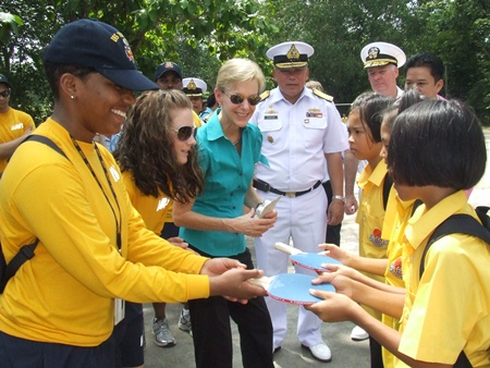 Sailors help Ambassador Kenney distribute sports equipment to local students.