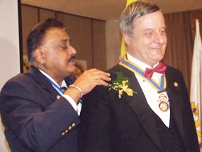 PDG Peter Malhotra presents the chain of office to President Yves Echement of the Rotary Club of Pattaya Marina.