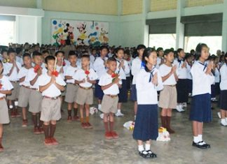 Students recite a Buddhist prayer and wai khru chant, which expresses respect and gratitude for the teachers and asks for their blessing of the students' studies.