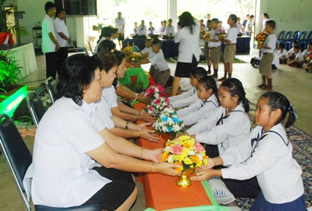 The students present trays of flowers, incense and candles to their teachers.