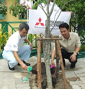 Hidetoshi Kan (left), managing director of Mitsubishi Elevator Thailand Co., Ltd., and Mayor Itthiphol Kunplome plant a tree to mark the 88th anniversary of Pattaya School #8.