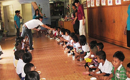 The young students dutifully line up to eat and enjoy the delicious snacks provided by the Human Resources team from Sheraton Pattaya Resort.