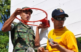 Ban Chang (May 12, 2011)- Fireman Giovanni Santiago, of USS Tortuga (LSD 46), waits for tools while he and a Royal Thai marine hang a basketball goal at the Wat Sombonaro School. USS Tortuga, USS Ruben James (DDG 57) and USS Howard (DDG 83) sent more than 30 Sailors to the school to help preserve a bathroom and refurbish a playground as a community service project for CARAT Thailand 2011. (U.S. Navy photo by Lt. K. Madison Carter)