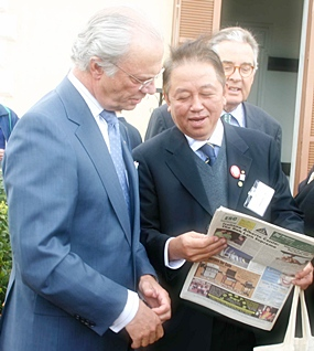 Sutham Phanthusak, commissioner of the National Scout Organization of Thailand, shows King Carl VI Gustav of Sweden our front page when we featured him visiting their Majesties the King and Queen of Thailand to say thank you for help for the tsunami victims.  The man in the background is the chairman of the World Scout Foundation, Dr. Eberhard Von Koerber.  The pic was taken at a Scout camp outside Rome April 22, 2005.
