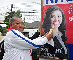 Out campaigning on a hot day, Pheu Thai candidate Adm. Surapol Chandang jokingly offers a cool drink to Prime Minister candidate Yinglak Shinawatra's poster.