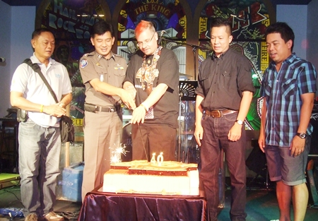 "Mathew ""Matty"" Carley (center), Hard Rock Cafe manager, and honored guests cut the birthday cake."