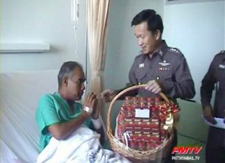 Injured police senior sergeant major Thatpong Thongthat receives a gift from Chonburi Provincial Police Maj. Gen. Thanet Pinmuangam