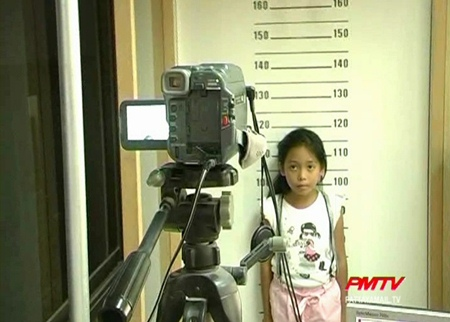 One young girl gets her picture taken for her 1st ID card.