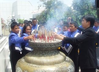 The young band members join in the ceremony by lighting and placing joss sticks in the ceremonial urn in front of City Hall.