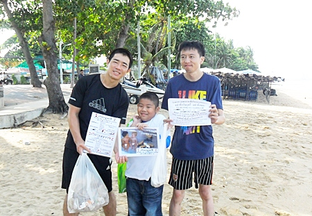 Two Chinese gentlemen and Phu are helping to clean trash off Jomtien Beach.