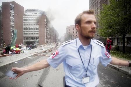 An official attempts to clear away spectators from buildings in the center of Oslo following an explosion that tore open several buildings including the prime minister's office, shattering windows and covering the street with documents. (AP Photo/Fartein Rudjord)